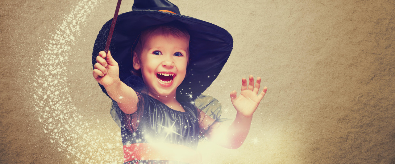 Halloween. cheerful little witch with a magic wand and glowing